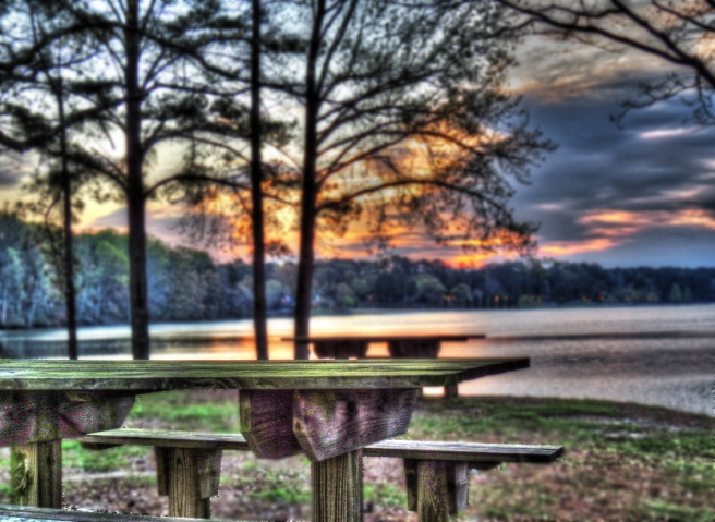 empty park bench at sunrise at the lake